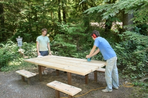 Volunteers refinishing one of three tables
