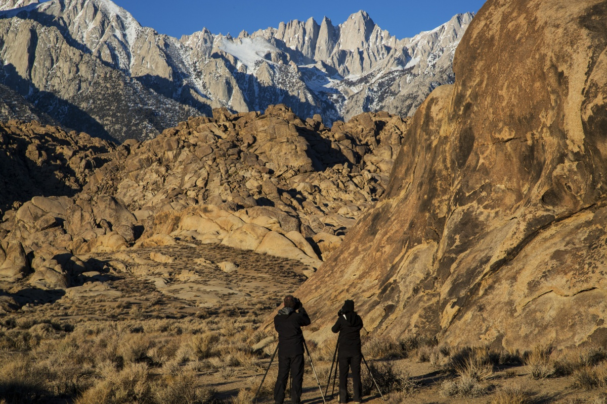 Two visitors photograph the mountains at Alabama Hills in California. Photo by Bob Wick, BLM.