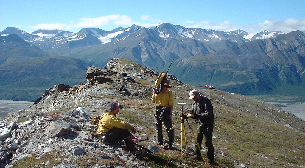 Three cadastral surveyors work on the top of a mountain with a landscape view. BLM photo.