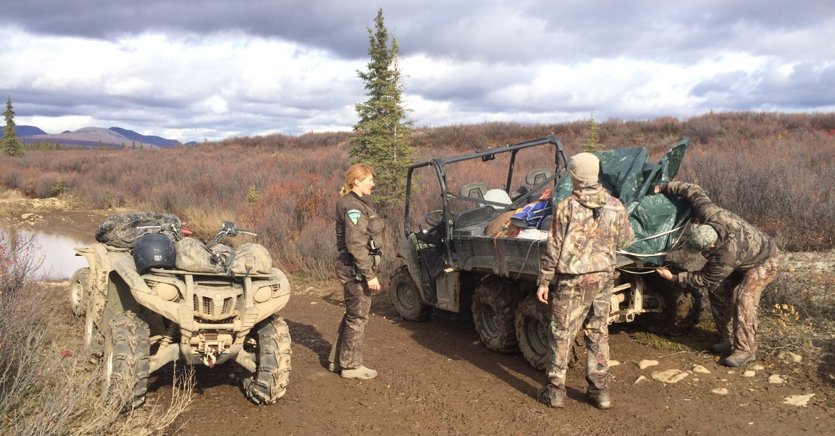 A BLM ranger helps two hunters.