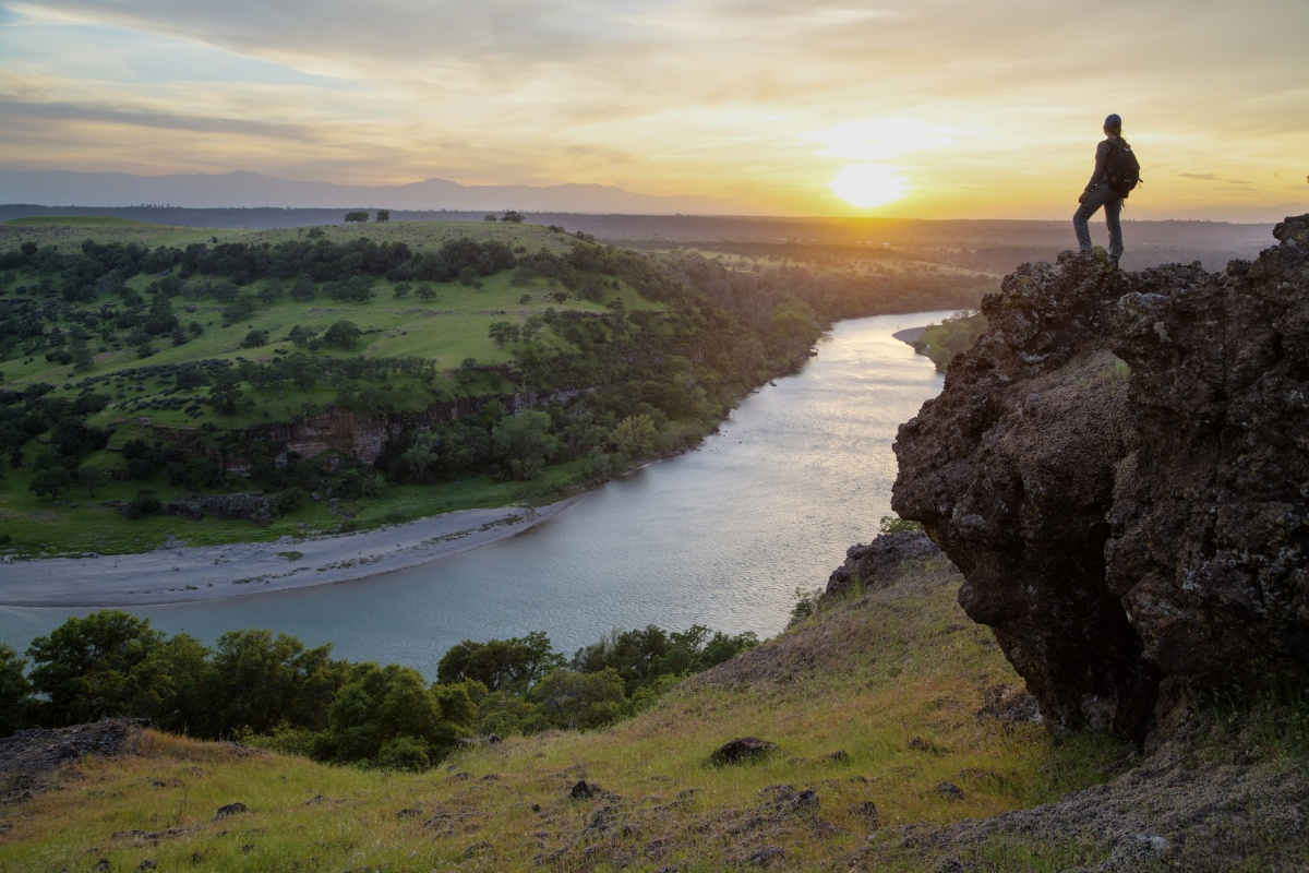 A women looks over the Sacramento River Bend Outstanding Natural Area in California at sunset, photo by Bob Wick, BLM