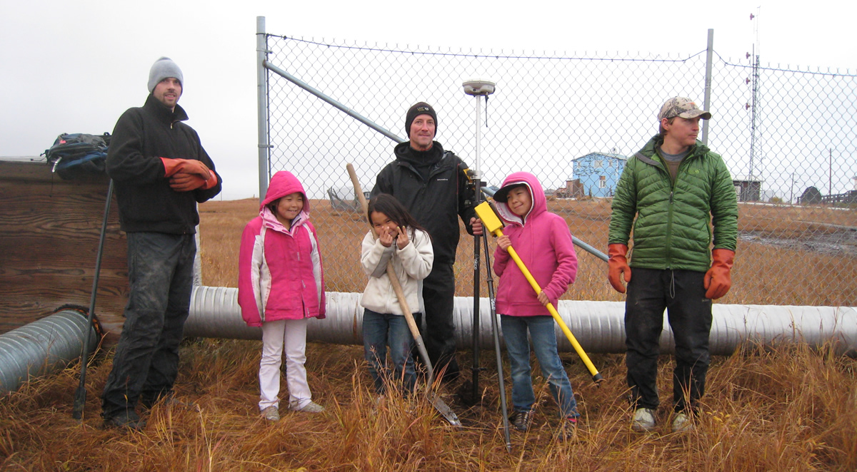 BLM Alaska surveyors buddled up standing with kids in Chevak, Alaska