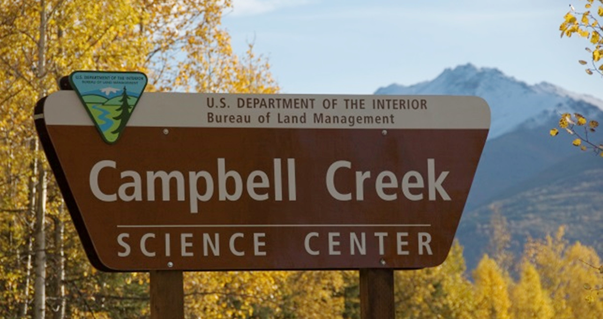 BLM Campbell Creek Science Center Sign in the fall. Birch tree leaves are all yellow.