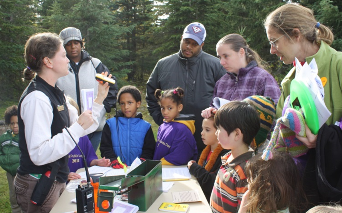 Kids and their parents listen to instructions about GPS as they get ready for a GPS-based activity at a Science Center Open House.