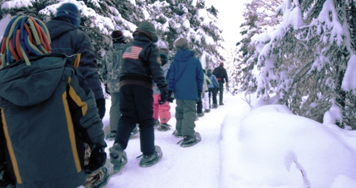 A line of students on snowshoes follows an instructor through the snowy forest on Campbell Tract.