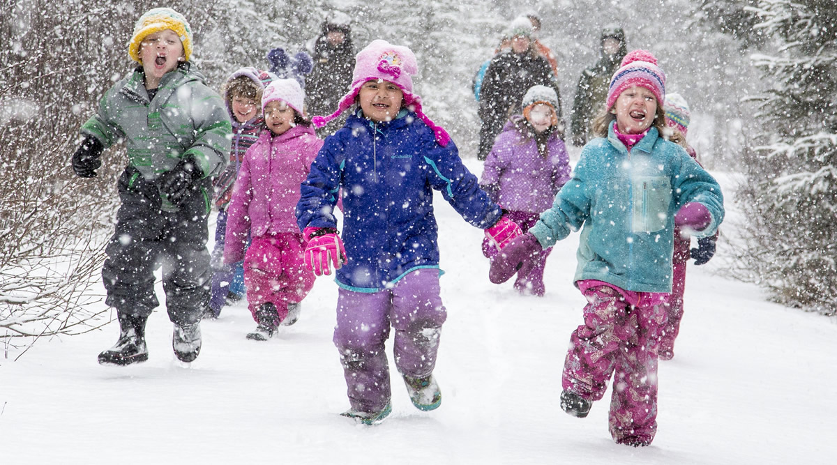 Excited children run through the snow down the trail during a program at the Campbell Creek Science Center.