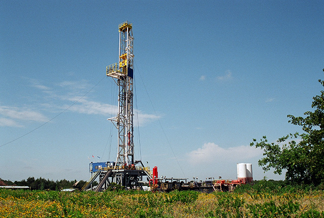 Drilling rig in Oklahoma with grass and small sunflowers in the foreground