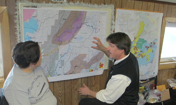Anchorage Field Manager talking to village member in front of map of planning area