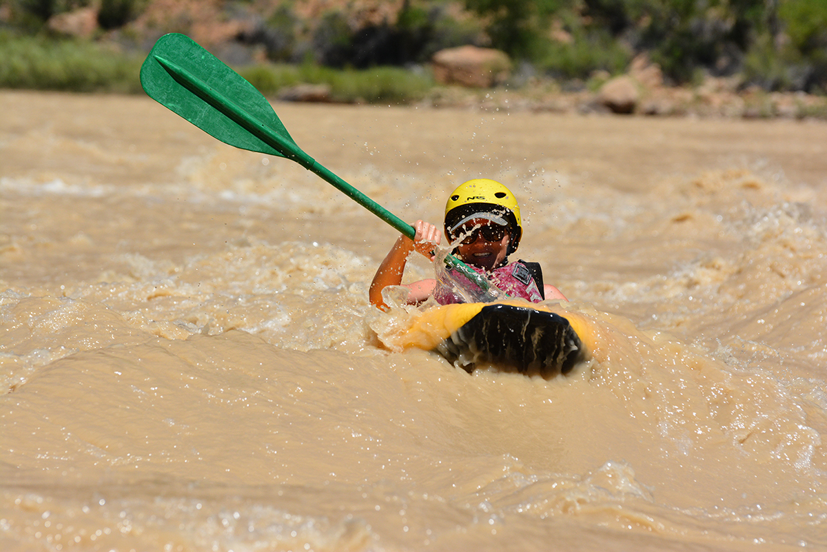A woman paddles through whitewater rapids in her inflatable kayak.