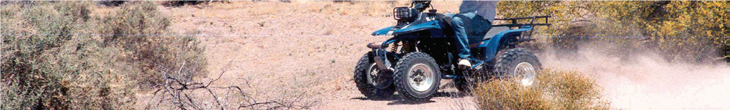 man in blue jeans drives ATV on narrow dirt road