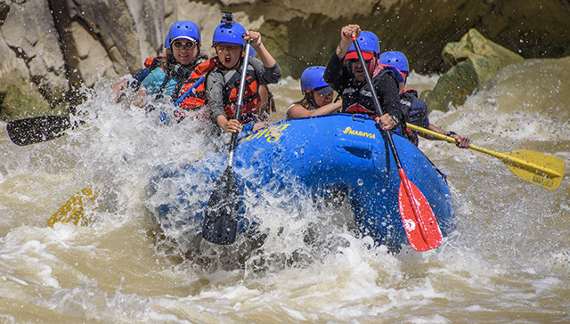 A group enjoys paddling through the whitewater rapids in the Westwater Canyon.