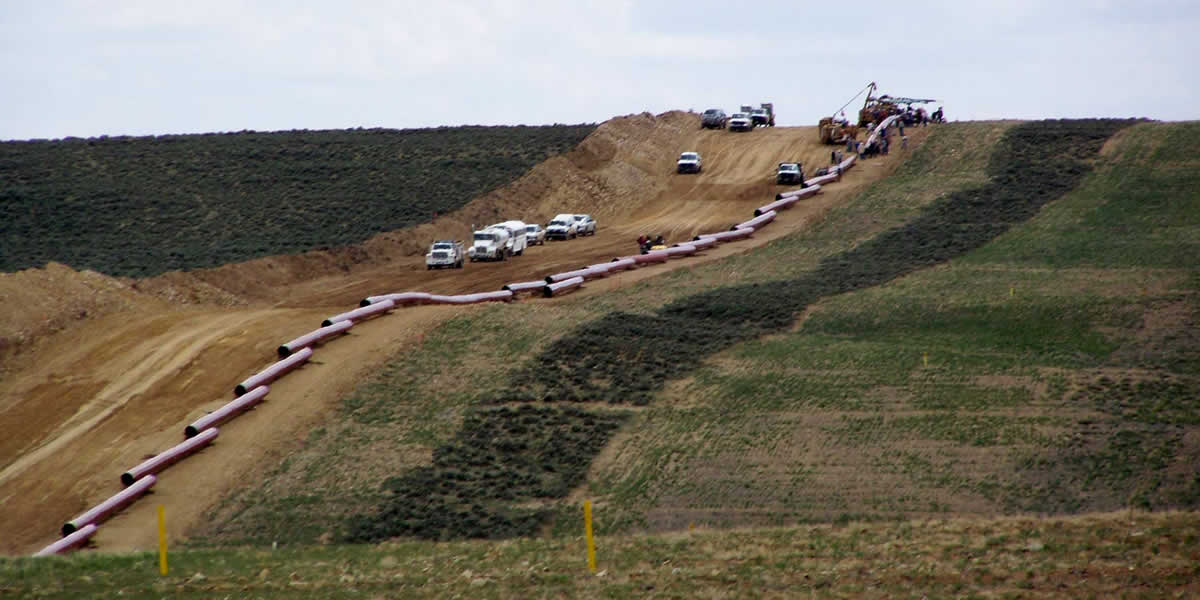 A dirt road goes through the center and a line of large pipes is alongside.