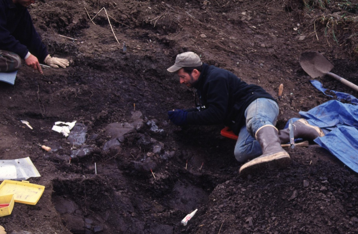 Dr. Anthony R. Fiorillo laying down in the dirt using hand tools unearthing Pachyrhinosaurus perotorum fossils, along the Colville River. Photo by courtesy of Dr. Anthony R. Fiorillo and the Museum of Nature and Science in Dallas.