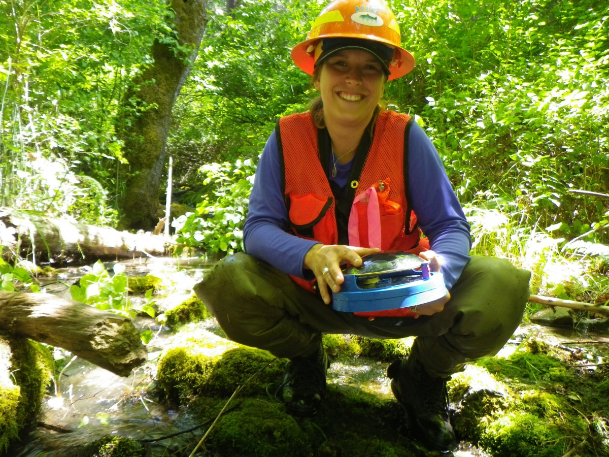 A female BLM employee takes time for a photo as she conducts water experiments in a local river. BLM photo.