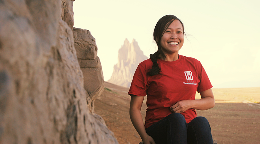 An employee smiles against a mountainous landscape. BLM photo.