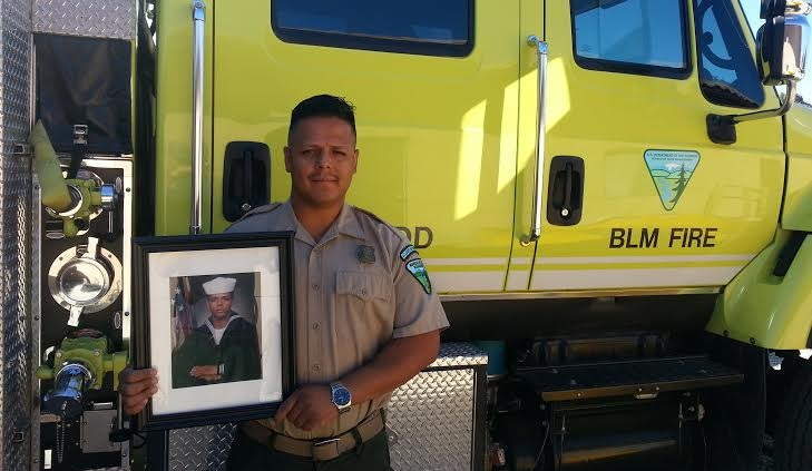 A BLM employee stands next to a firetruck, holding his military photo.  BLM photo.