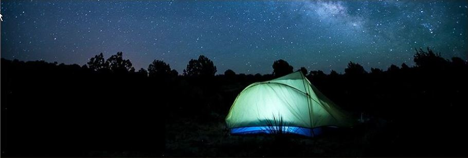 Illuminated tent in front of a darkened, star-filled sky