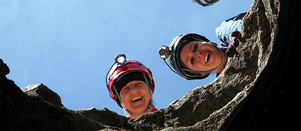 Two smiling people stare down into the camera as they lean over the edge of a rocky ledge