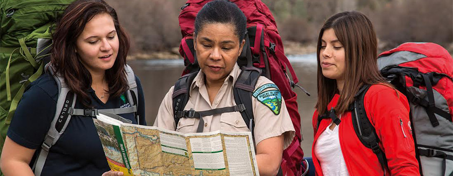A trio of back pack wearing BLM female employees are reading a map