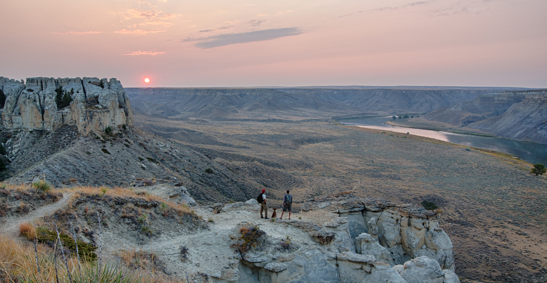 Hikers watch the sun set along the Upper Missouri River.