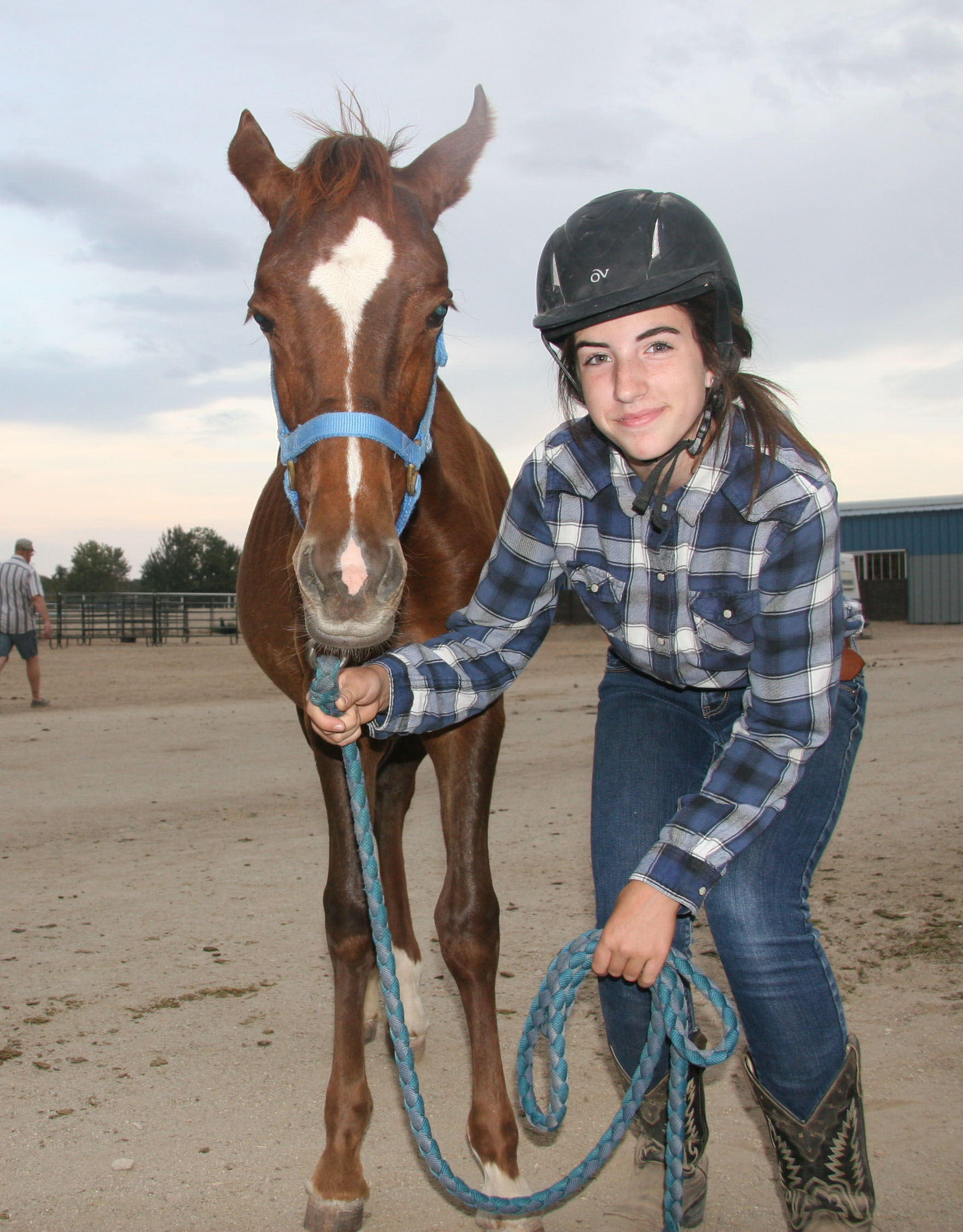 An Idaho 4-H member stands proudly with the mustang she is gentling as part of the partnership with BLM.