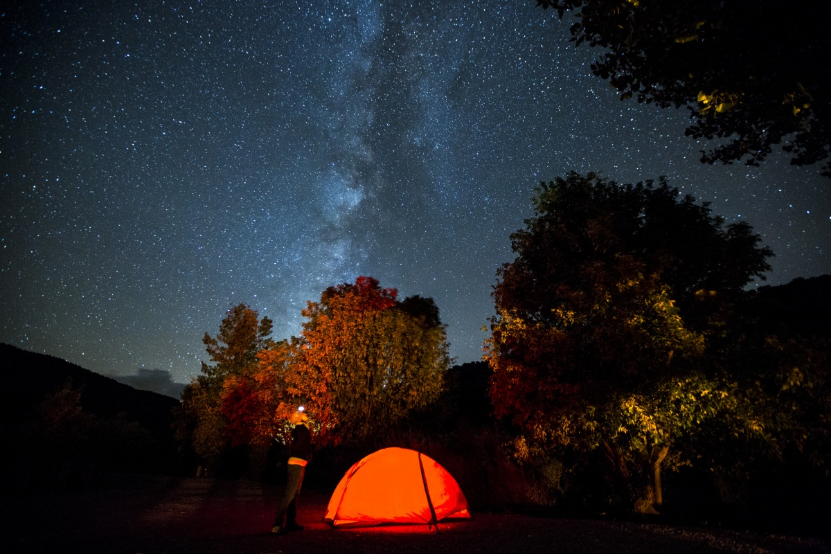 A women stands near her tent and admires the milky way in New Mexico. Photo by Bob Wick, BLM.