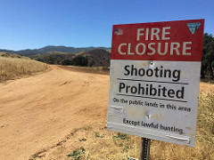 A sign near a dirt road tells visitors of a fire closure and shooting restrictions in the area.  Photo by Michelle Puckett, BLM.