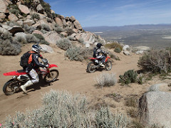 Two motorcycle riders on a dirt road leading through a mountain area overlooking a valley.  Photo by Marisa Williams, BLM.