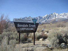 A BLM sign at the entrance to the Goodale Creek Campground with snow covered mountains in the background (BLM Photo).