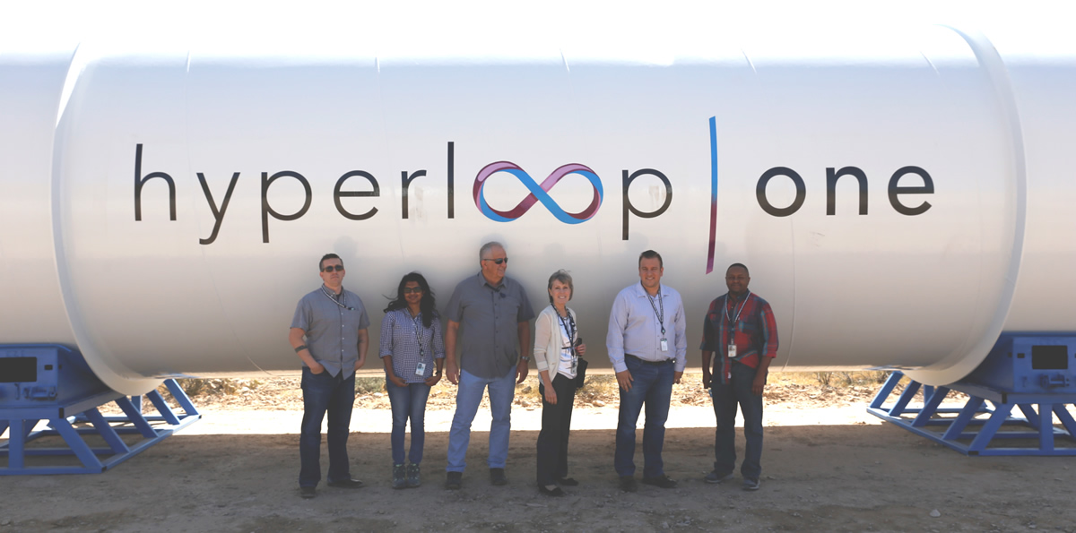 Six Las Vegas Field Office (LVFO) employees in front of a Hyperloop One tube.