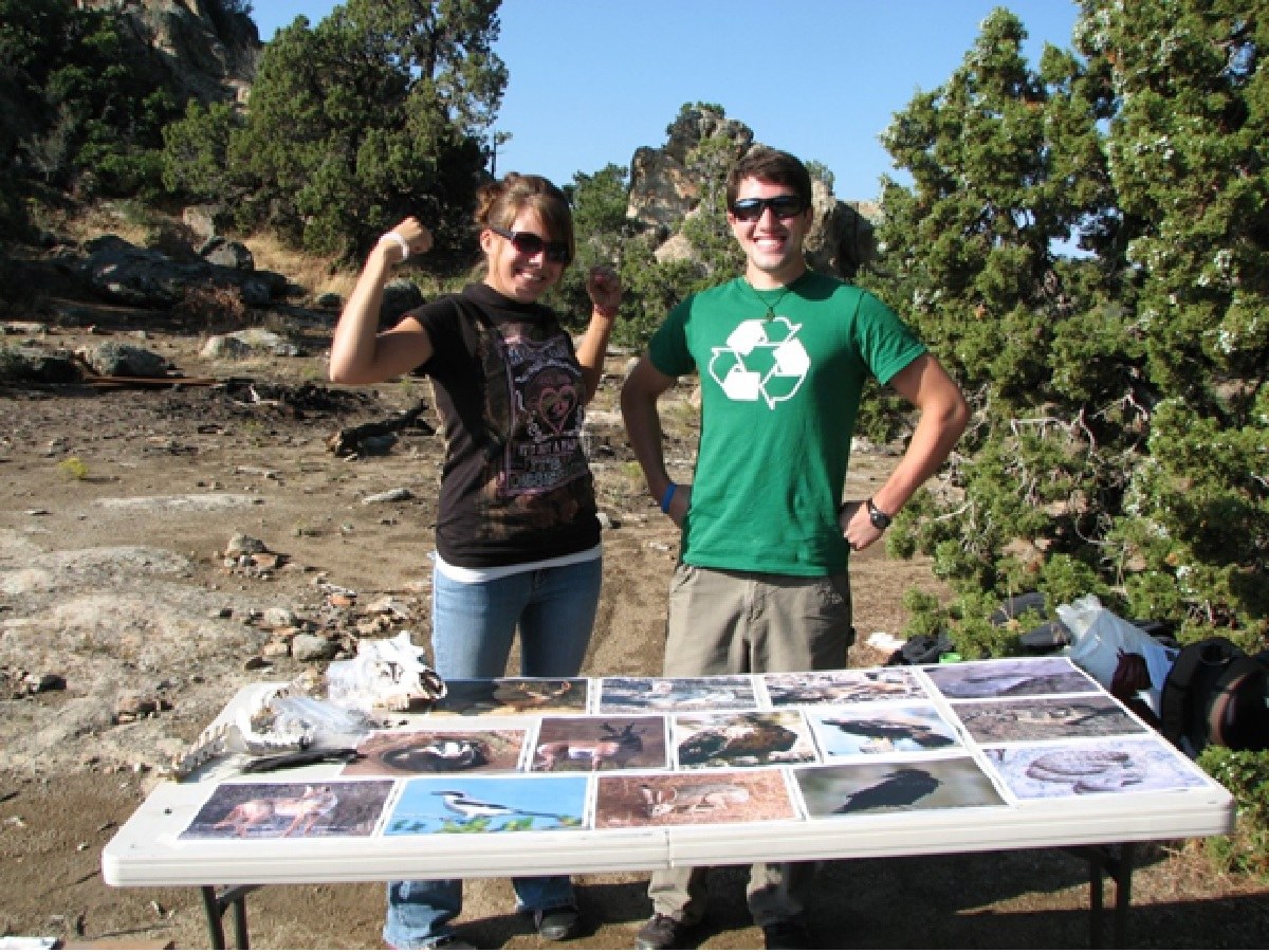 A man and woman in the field pose behind a foldable table covered with photos of birds.
