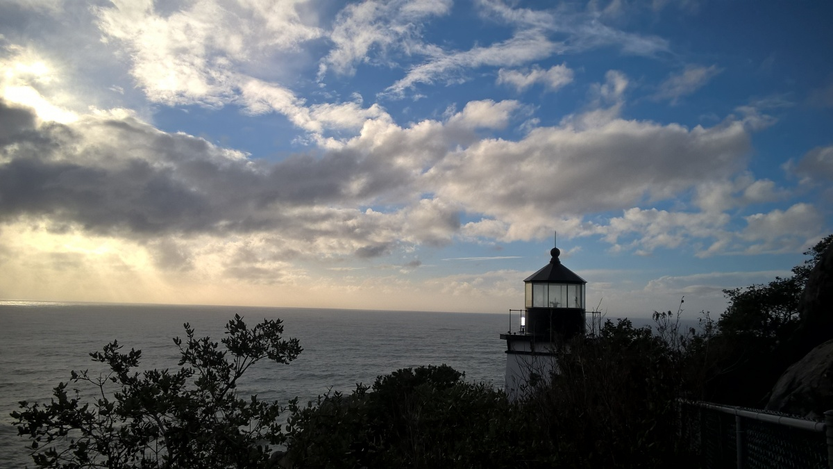 The lighthouse at Trinidad Head.  The lighthouse  overlooks the ocean. The sun shines through the clouds.