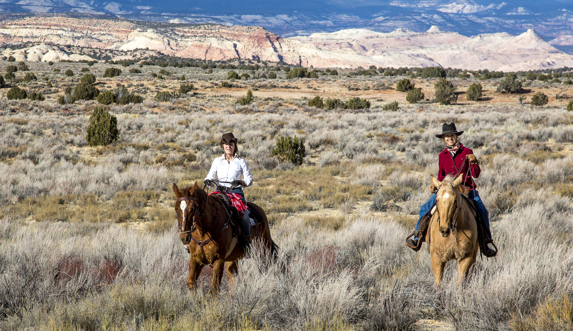 Two women ride horses through grasslands in the Grand Staircase-Escalante National Monument. Photo by Bob Wick