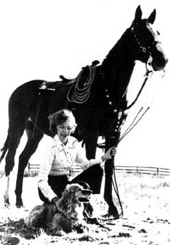 Velma B. Johnson (also known as Wild Horse Annie) kneels next to a horse. BLM photo.