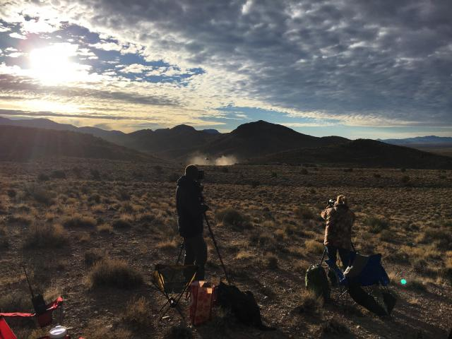 Members of the public (foreground) watch as the helicopter pilot (background) shepherds wild horses toward the trapsite.