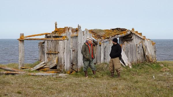 Two men stand in front of a sod home built of drift wood and whale bones with the Arctic ocean in the background