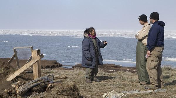 A woman speaking to two men, All are standing near an excavation site with the Arctic Ocean in the background