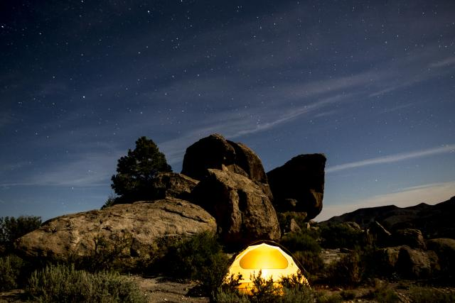 Illuminated tent near a rocky background and starry night