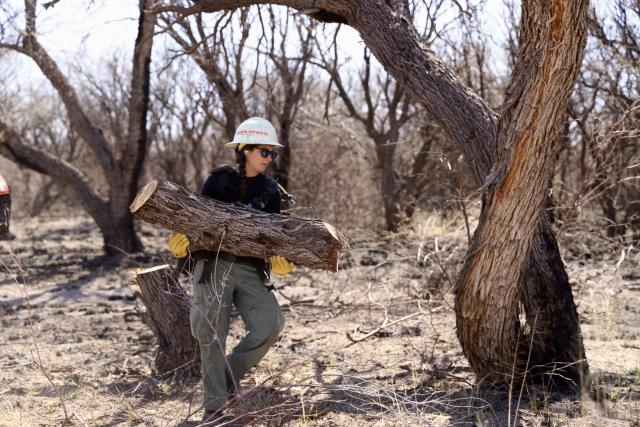 a firefighter carries a large log