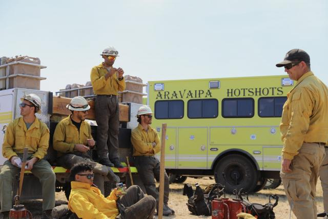 a group of firefighters eat lunch. A truck in the background reads Aravaipa Hotshots.