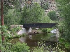 A rail bridge over a forest creek.  Photo by Jeff Fontana/BLM
