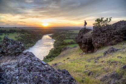 Woman standing on a rock overlooks sunset over river