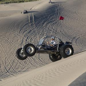 Dune buggy doing a wheely in the sand dunes
