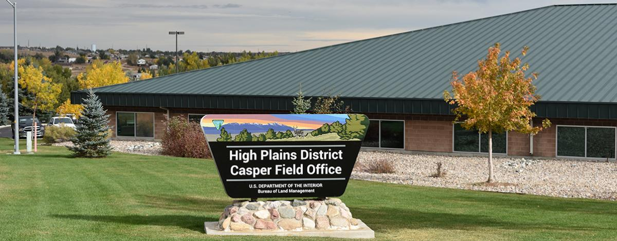 The road sign for the High Plains District Office, with the building, fall foliage and the City of Casper in the background.