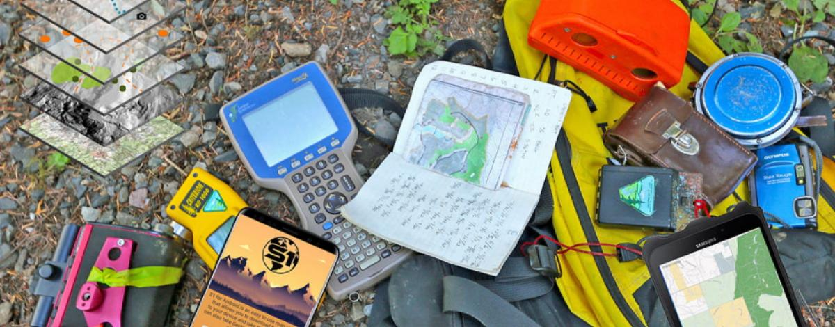 A selection of gear used for field data collection laying on the ground, including paper and electronics