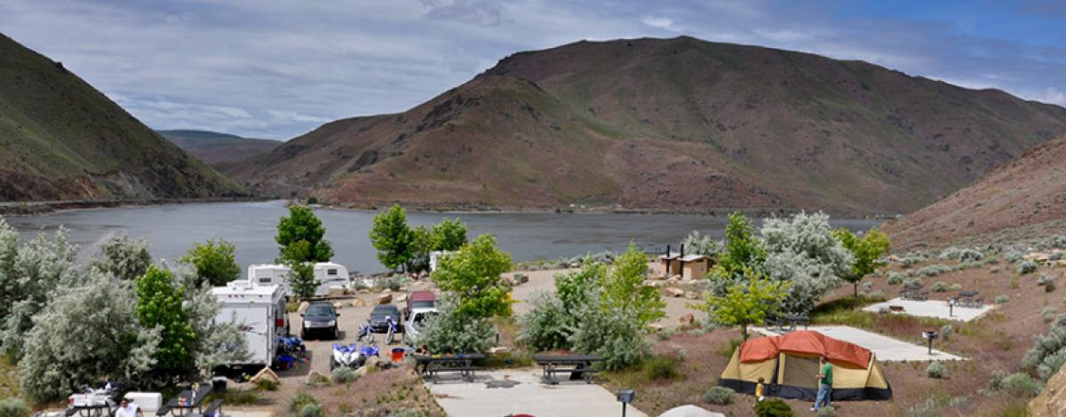 A campgroup along a lake in Idaho with concrete bases for tents, RVs, camp chairs, and tents scattered through the sites with trees spread throughout. A pit toilet and other amenities are also onsite.