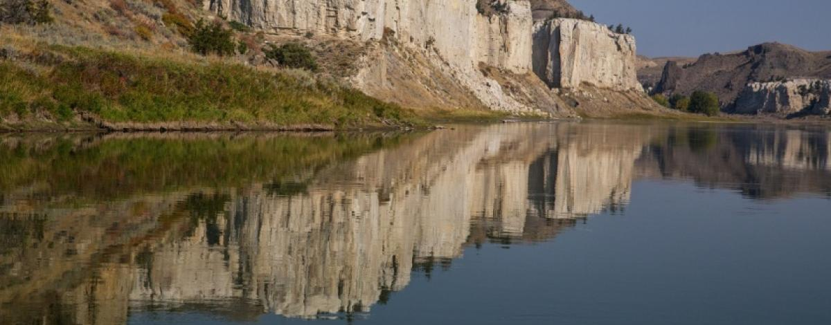 The majestic cliffs of Upper Missouri Breaks National Monuments reflected in the Missouri River. Photo by Bob Wick.