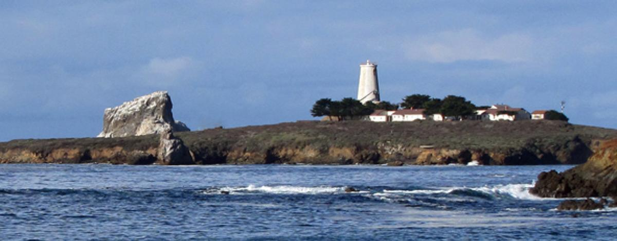 A lighthouse and several buildings sit on a peninsula in the Pacific Ocean.  (BLM Photo)