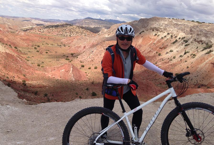 A cyclist standing in front of the red rock canyon at White Ridge Bike Trails