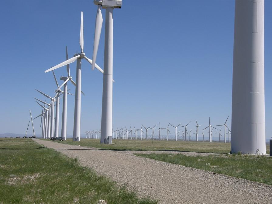 Image shows wind turbines set in a grassy field actively spinning under a clear blue sky.